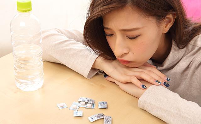 頭痛薬を前に悩む女性